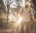 Handsome traveler with hiking poles in autumnal forest backpack and Royalty Free Stock Photo
