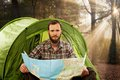 Handsome traveler near tent with a map Royalty Free Stock Photo