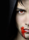 Handsome vampire portrait of an over a black background Stock Photos