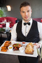 Handsome waiter serving appetizing finger food platter in classy restaurant Royalty Free Stock Photos