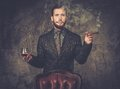 Handsome well dressed man with glass of beverage and cigar Royalty Free Stock Photo