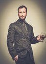 Handsome well dressed man with glass in jacket of beverage Royalty Free Stock Images