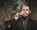 Handsome well dressed man smoking with glass of beverage and cigar Stock Image