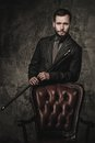 Handsome well dressed man with stick standing near leather chair Stock Photography