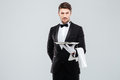 Handsome yong waiter in tuxedo and gloves holding empty tray