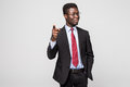Handsome young African man in formalwear pointing on you while standing against grey background Royalty Free Stock Photo