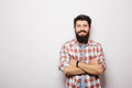 Handsome young bearded man holding crossed hands  and looking at camera Royalty Free Stock Photo