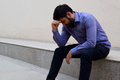 Stressed and sad young man sitting outside holding head with a hand looking down. Human emotion feelings, sad bearded man Royalty Free Stock Photo