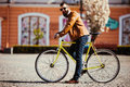Young bearded man hipster in sunglasses leaning at his bicycle and looking away while standing on city street