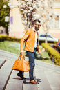 Handsome young bearded man in sunglasses walking down on the stairs with bag on city outdoors Royalty Free Stock Photo