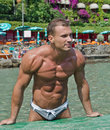 Handsome young bodybuilder on the beach attractive muscular man getting out of water with sea or ocean behind Stock Image
