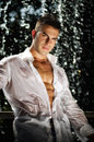 Handsome young bodybuilder standing in front of waterfall attractive muscle man with wet open shirt Stock Photos
