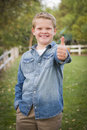 Handsome young boy giving the thumbs up in park Stock Images
