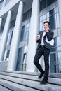 Handsome young businessman is going out from his successful man in suit moving on steps outdoors he talking on the phone and Stock Photography
