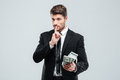 Handsome young businessman holding money and showing silence sign Royalty Free Stock Photo