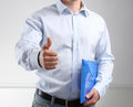 Handsome young businessman showing ok standing with folder Royalty Free Stock Photo