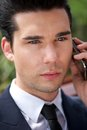 Handsome young businessman talking on phone close up portrait of a the outdoors Stock Image