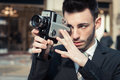Handsome young businessman using a vintage film camera in suit and tie Stock Photo