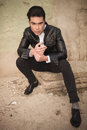 Handsome young fashion man sitting near a wall Royalty Free Stock Photo