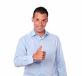 Handsome young guy with ok sign portrait of a on blue shirt standing and smiling at you on isolated studio Royalty Free Stock Image