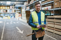 Handsome young handyman in a warehouse or supervisor standing amongst the building supplies with tablet his hand smiling at the Stock Photography