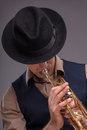 Handsome young jazz man close up portrait of a in a suit with a black hat hiding his face and playing a trumpet isolated on grey Stock Images