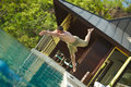 Handsome young lifeguard plunge in swimming pool to rescue. Royalty Free Stock Photo