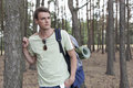Handsome young man with backpack hiking in woods Stock Photo