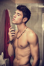 Handsome young man in bathroom spraying cologne his home or perfume on neck Royalty Free Stock Images