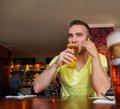 Handsome young man drinking beer in a pub with mobile phone and Royalty Free Stock Photo