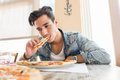 Handsome young man eating pizza at home wearing casual denim shirt low angle perspective Royalty Free Stock Photos