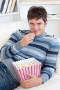 Handsome young man eating popcorn lying on sofa Stock Images