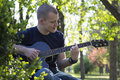 stock image of  Handsome young man enjoying the park with a guitar