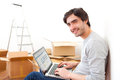 Handsome young man in his new flat using laptop view of a Royalty Free Stock Image