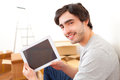 Handsome young man in his new flat using tablet view of a Royalty Free Stock Photos