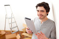 Handsome young man in his new flat using tablet view of a Stock Photography