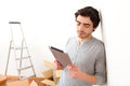 Handsome young man in his new flat using tablet view of a Royalty Free Stock Photography