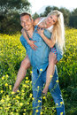Handsome young man with his pretty girlfriend men blond having a relaxing day in the countryside giving her a piggy back ride Stock Image