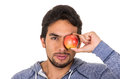 Handsome young man holding red apple closeup latin in front of his eye isolated on white Stock Photos