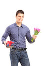 Handsome young man holding tulips and gift box isolated on white background Stock Photo