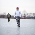 Handsome young man ice skating outdoors on a pond Stock Image