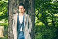 Handsome young man leaning against tree Royalty Free Stock Photo