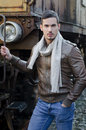 Handsome young man in leather jacket and jeans next to old train attractive looking at camera Stock Image