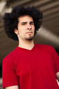 Handsome young man with long curly hair and goatee in a outdoor urban setting Stock Images