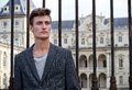 Handsome young man outside elegant palace leaning on gate Royalty Free Stock Images