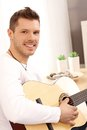 Handsome young man playing guitar Stock Image