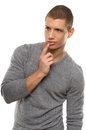 Handsome young man posing and with the index finger touching the lips Stock Images
