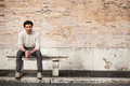 Handsome young man sitting on marble bench with bricks background Royalty Free Stock Photo