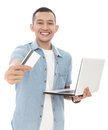 handsome young man smiling while showing a credit card and holding a laptop