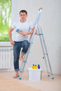 Handsome young man standing near ladder holding paintbrush and looking at camera Royalty Free Stock Photos